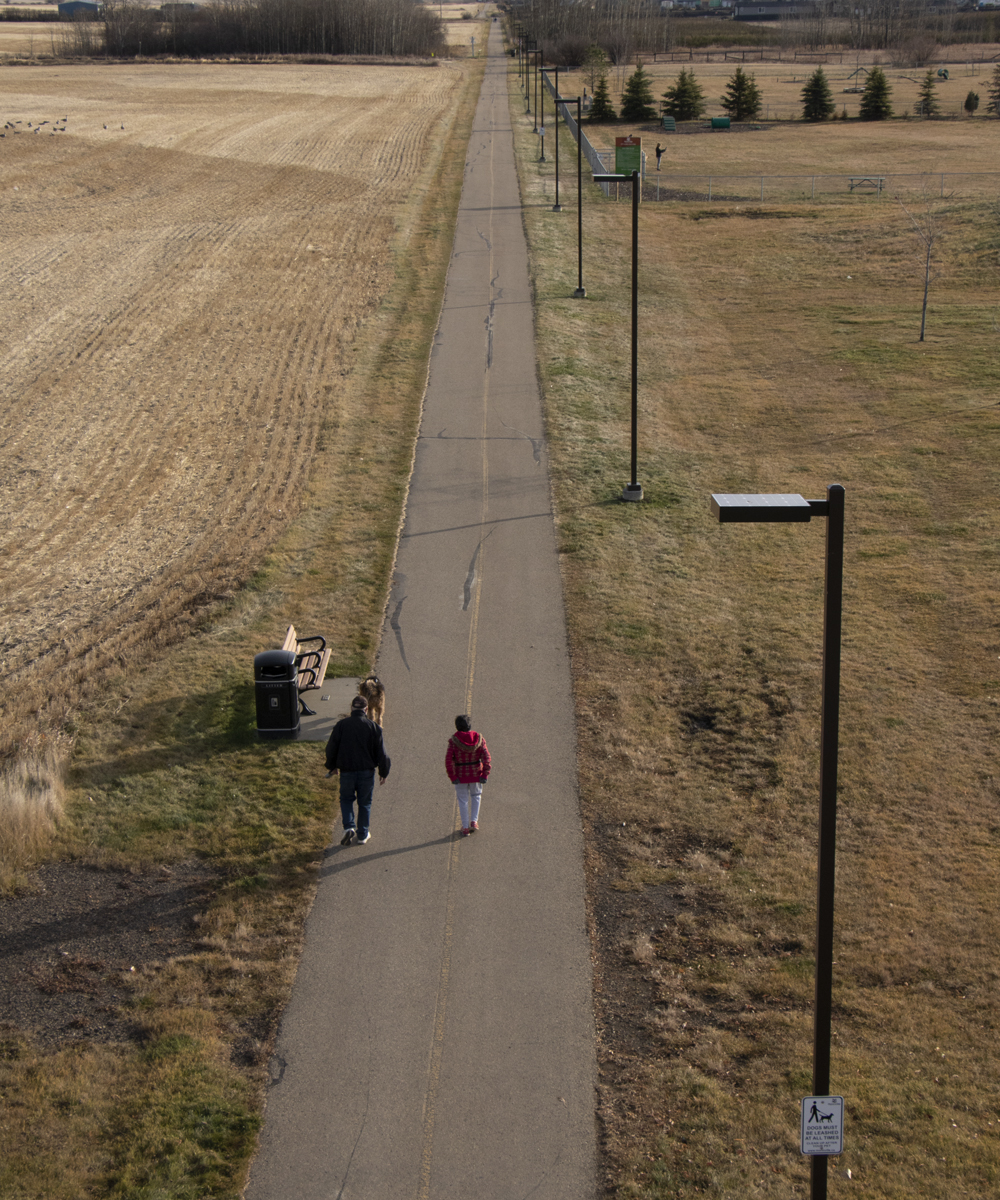 people walking on pathway with solar lighting beside - First Light Technologies